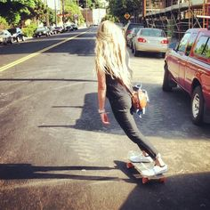 Cool style. A seriously MEAN LEAN on that cruiser. Black slim jeans rolled up, black tank, white Chucks. GREAT picture. Captures the essence and freedom of a simple cruise and simple style. This makes me wanna skate down the street. DOPE.