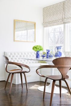 Amazing breakfast nook is filled with an built in banquette upholstered in white tufted vinyl situated under windows dressed in taupe chevron fabric by Holly Hunt facing a Saarinen Oval Dining Table lined with Cherner Armchairs atop wood floors laid out in herringbone pattern.