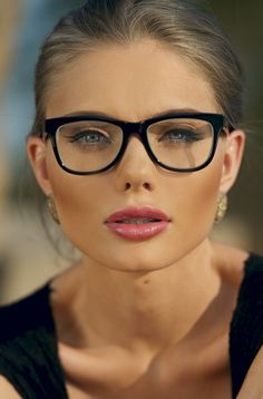 blue eyes, glasses, hair pulled back to enhance the flawless makeup and bone…