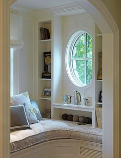 My mother would have adored a reading nook like this. It's got everything--window seat, pretty porthole window and shelves for knick knacks