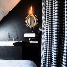"""Une salle de bains noire. Petite mais confortable, la chambre intègre la salle de bains qui se fait oublier grâce au mur sombre et au pourtour de la baignoire recouvert de béton ciré noir, une couleur """"aussi neutre que le blanc"""", assure Laurence.     Miroir en bois doré, meuble lavabo en acier laqué noir réalisé sur mesure. Applique, House Doctor, serviettes en lin AM.PM. Linge de lit, Maison de Vacances."""