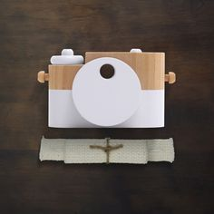 Pixie Camera in Cotton  Help your kids play better by encouraging them to ditch the screen and toy with nature.  One in a vibrant, new collection of our classic wooden camera, with movable knobs, buttons, and a rotating view finder. Handcrafted from eco-friendly materials and paints. Each measures approximately 3.5 x 2...