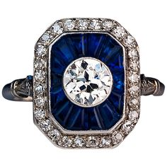 circa 1915  A vintage platinum milgrain ring of a rectangular shape with cut corners is centered with a bright white old European cut diamond (5.5 x 3.35 mm, approximately 0.66 ct, I color, VS1 clarity) outlined by a row of tapered calibre cut deep blue sapphires and further set with a border of old single cut diamonds (approximately 0.45 total weight).