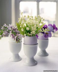 Egg cups, eggs, and delicate flowers create a charming arrangement; could be separated and each one used for an individual nosegay for each place setting.