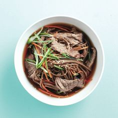 Japanese beef and soba bowl - 3 bundles soba noodles (about 1 in. each), abt 300 g; 1 carrot, peeled and julienned; 2 c no-salt beef broth; 1/4 c seasoned rice vinegar; 2 tbsp low-sodium soy sauce; 4 tsp honey; 250 g strip loin steak, very thinly sliced; 4 green onions, thinly sliced; 2 tbsp toasted sesame seeds