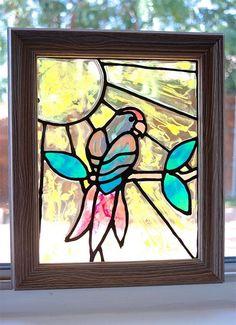 peinture sur verre avec un tableau encadré un perroquet sur branche dessiné au fond jaune