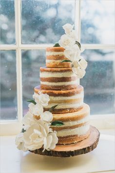 Naked wedding cake with white flowers and white frosting @weddingchicks