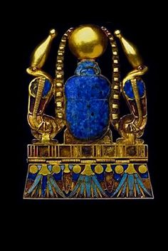 Ancient Egyptian jewelled scarab amulet with the cobras of protection on each side wearing the crown of Upper Egypt; the lotus & suns on bottom edge represent immortality egyptian-scarab-amulet-439x657
