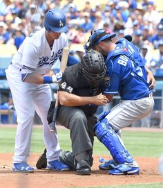Umpire Kerwin Danley is helped by Cody Bellinger #35 of the Los Angeles Dodgers and Drew Butera #9 of the Kansas City Royals after getting hit in the face mask in the first inning at Dodger Stadium on July 9, 2017 in Los Angeles, California. pinterest// samparra515