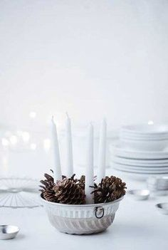 Christmas table decorations with pine cones and candles.