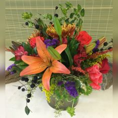 """Our popular Uptown Vase in fall tones.  Designed in a 6"""" low cylinder vase using Autumn's best blooms, textural fillers and foliage. Just like the changing season, product may vary with availability as fall progresses.  Higher price points will include more floral content to value. Same Day Flower Delivery, Cylinder Vase, Floral Design, Bloom, Content, Seasons, Popular, Texture, Fall"""