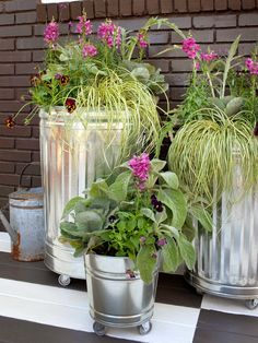 galvanized steel trash cans as flower pots -- use krylon exterior spray paint to make them match your outdoor color scheme