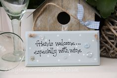 Handmade plaque decorated with buttons.  Sign reads 'Friends welcome...especially with wine'.