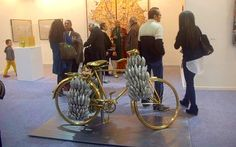 Subodh Gupta's untitled work, showcased by Nature Morte. The cycle is made from brass and laden with bananas crafted from aluminium.