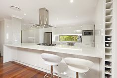 Minimalistic Kitchen with no handles, 2pac finishes, caesarstone, feature tiled column, stainless steel appliances, canopy rangehood, gas cooktop and window in kitchen.
