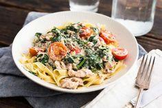 Recept voor verse pasta voor 4 personen. Met zout, olijfolie, peper, verse tagliatelle, zalm uit blik, kruiden-roomkaas, verse spinazie, ui en cherrytomaat