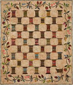 Spools of sweet quilted thread...looks like it's snowball blocks with string pieced sashing...and beautiful appliqué!  Love it!