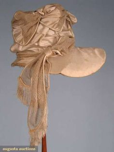 """Ivory silk hat, c1820; Satin, deep crown and wide brim, buckram form, decorated with wide ribbon fashioned from pieced satin and looped silk gauze, fine silk fringe on ends of ribbon, provenance Ten Eyck family, Brim Wd 14.5"""", Crown Ht 5.5"""""""