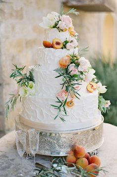 A stunning textured white wedding cake features fresh peaches and pastel-colored blooms for a rustic outdoor wedding.