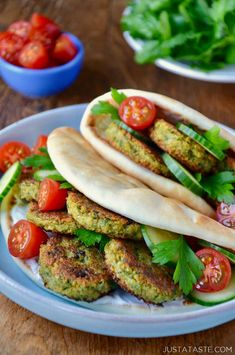 Easy Homemade Falafel tucked inside pita bread with Tahini Sauce, cucumbers, tomatoes and parsley. Small blue blue with cherry tomatoes and white plate with chopped parsley in background.