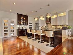 Cuisine classique blanche et brun. Magnifique îlot en marbre brun. On adore le dosseret des armoires en mosaïque avec les armoires blanches.
