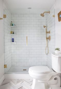 white #subway #tile #bathroom shower with gold faucets