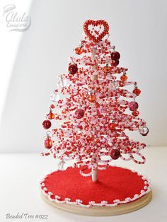 This Miniature Valentine Tree become great Valentines gift, Valentines day decor, Valentines centerpiece, Mothers Day Gift, and doll house decor.  This Beaded Tree comes with a beaded Open Heart, crystal bead ornaments, acrylic bead ornaments and a tree skirt.  > Approximate Dimensions: - Diameter 4 1/2 inch (12cm), - Height 7 inch (18cm),  > Colors - Star : Silver Lined Red - Tree : Pink Red White Mixed - Skirt : Red - Base Plaque : Natural color Polyurethane Finish  - Due to the ...