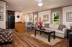 The warm tones and the beautiful hardwood floor really make this living room/kitchen/dining room look spacious! #modularhome #modularhomesinpa #homedesign #housedesign #floorplan #openconcept #homedecor #livingroomdecor