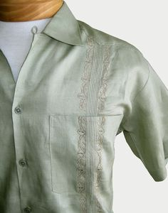 Close-up of one of our men's linen Guayabera shirts, showing the gorgeous hand-embroidered details. These handsome, button-up shirts are perfect for any occasion. 100% linen, in a light sage green or khaki color. They include short sleeves, a collar, and four pockets. Get one for Father's Day! See more at: www.elinterior.com