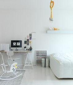 A brilliant white floor allows the smallest hints of neon color to pop in this Scandinavian bedroom. Bright white makes even small rooms look spacious, and employing one color throughout keeps costs down for a bedroom overhaul.