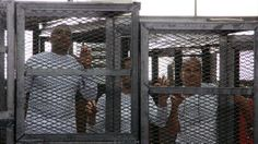 Al-Jazeera English bureau chief Mohamed Fahmy, left, producer Baher Mohamed, centre, and correspondent Peter Greste, right, appear in the courtroom along with several other defendants during their trial on terror charges in Cairo on March 31. Prime Minister Stephen Harper is now breaking his silence on the way Fahmy was treated.