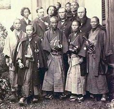 A group of samurai with three foreigners in the middle.