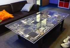 "This contemporary coffee table showcases the ""guts"" of an old computer.  Motherboards and other pieces of electronics are glued to an old wood coffee table.  The tabletop is a sheet of heavy #plexiglass elevated by acrylic standoffs."