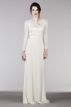"""Our play on a long sleeved wedding dress, this elegant and modern dress has a plunge back with a layered front neckline and one-of-a-kind floral hand embroidery that cascades down the front bodice as well as along the sleeves. Its impossibly long silhouette will also elongate the bride.• Can be ordered and worn with the matching AH1000 embroidered belt.Made of 100% silk: • Top layer: Off white silk chiffon. • Lining: Cream silk charmeuse. • Comes with 1"""" eggshell satin sash. • Should be…"""