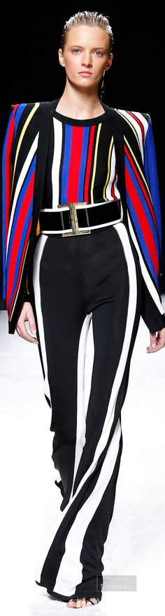 I am truly intoxicated with the design and colors of this outfit. We have bright fuchsia, cobalt blue, black and white stripes all vertical, on the top, and jacket. Then the pants are black and white, having the wide stripe of black.  Genius !!!