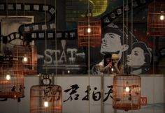 Chinese girls take pictures with their mobile phones outside a cinema near a bird cage decoration at a shopping mall in Beijing, China, July 29, 2012. (Andy Wong/Associated Press)     The Big Picture - Boston.com