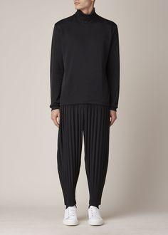 Long-sleeved black knit turtleneck in black poly cotton blend. Hand wash cold.