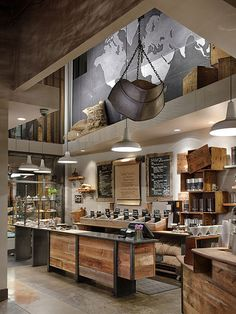 Love the industrial look. I see a stove in the island and huge stainless steel sink where the coffees are if you put it in a house.