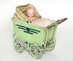 Little doll in a light green tin pram c. 1920.
