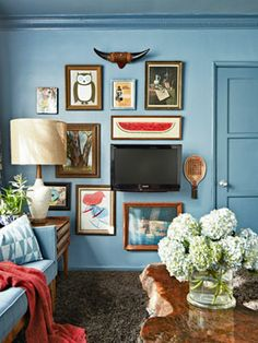 """Hide"" your flat-screen TV by surrounding it with square and rectangular pieces of artwork."