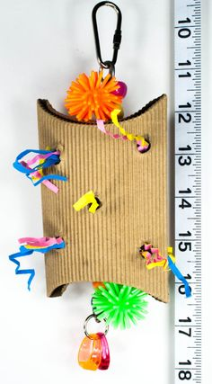 The Foraging Fun Box is a corrugated box stuffed full of colorful crinkle paper. Finished off with some spiny balls and plastic rings. Good for birds