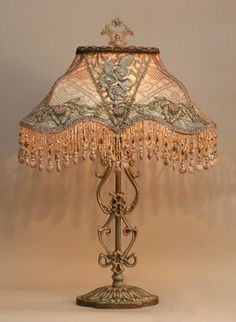 Artist Christine Kilger creates one-of-a-kind lamps. Using a antique lamp base that has been hand-painted and holds a hand-dyed Edwardian silk lampshade. The shade is ombre-dyed from pale champagne pink into pale blue. The shade is covered on the sides with coppery-gold metallic lace and the front is overlaid with beautiful Edwardian (Titanic era) floral passementerie and silver metallic handmade antique ribbon roses. The shade has hand beaded fringe in matching tones. #antiquelamps