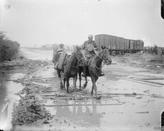 THE BATTLE OF PASSCHENDAELE, JULY-NOVEMBER 1917. Battle of Pilckem Ridge. Shell-carrying pack-horses splashing through the mud on a road north of Ypres, crossed by railway line, 1 August 1917.