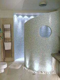 Curved walk in shower with river rocks.