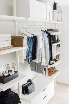 Shoes, bags and scarves are beautifully organized on modular shelves flanking a clothing rail positioned above modular drawers and below shelves holding white storage boxes in this gorgeous walk in closet.