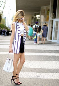 Black high waist shorts with white crop top, white bedford henri bendel drawstring bucket bag, occult collar baublebar necklace, rayban clubmaster sunglasses in gold and silver, tassel bracelets, and rebecca minkoff double strap sandals. Amanda Tur from A Fancy Affair blog, miami fashion blogger