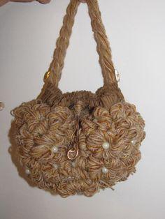 ciao a tutti.questa borsa è realizzata tutta con roselline di lana fatte interamente a mano più perline bianche.