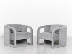 A pair of elegantlycurved clubchairs designed by Milo Baughman; each chairfeatures a removable backcushion for extra support. The chairs have been newly upholstered in a beautiful ashgrey vel…