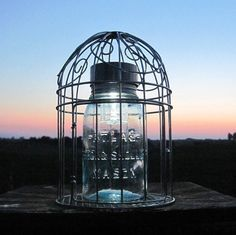 Upcycled mason jar solar light in a bird cage, unique and very pretty.