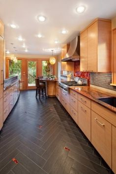Herringbone tile pattern. This pattern adds sophisticated visual texture to the floor. In this kitchen, bright glass tiles were added to match the glass backsplash behind the cooktop.